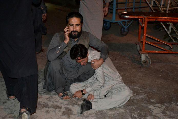 Een man troost een andere man die rouwt om de dood van een familielid in de brand in het Serenahotel in Pakistan.