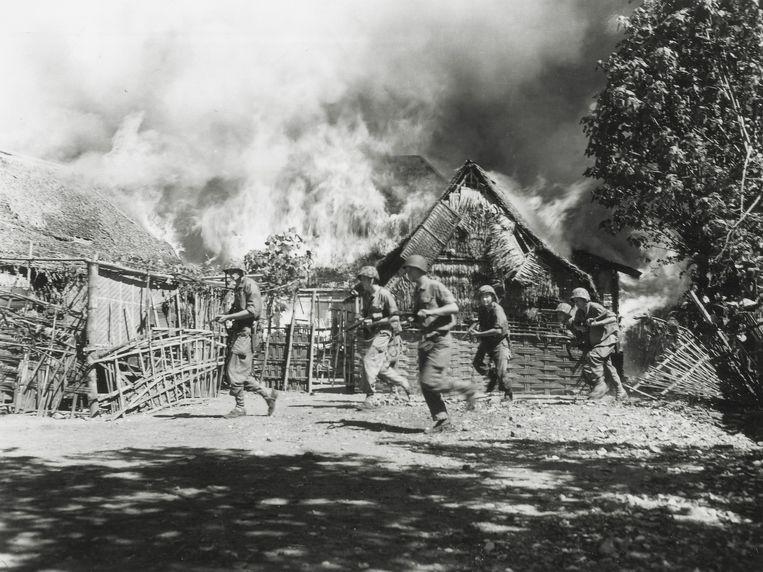 Nederlandse militairen op een brandende kampong op Oost-Java in 1946. Beeld Hugo A. Wilmar / Koninklijke Marine