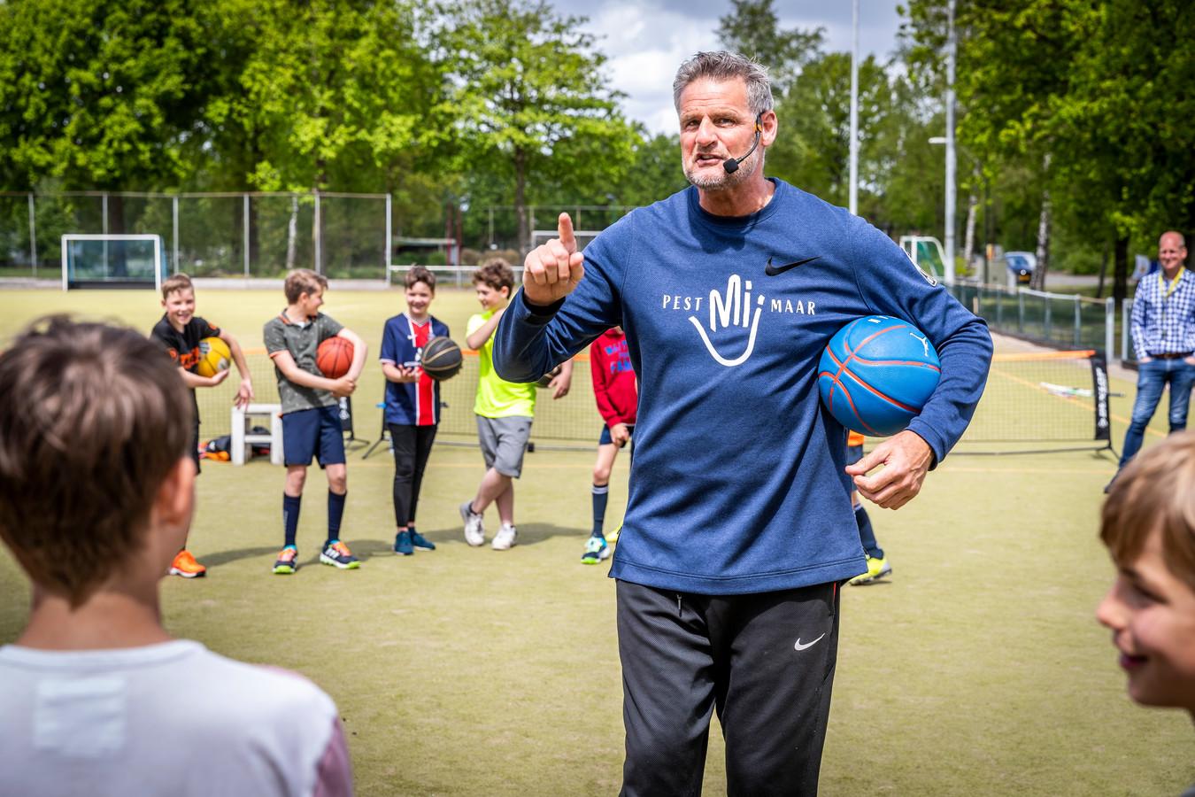 Oud-basketballer Henk Pieterse geeft een sportclinic aan kinderen in Maarheeze.