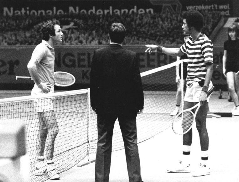 Het ABN AMRO World Tennis Tournament viert dit jaar - te beginnen komend weekeinde met de kwalificaties - zijn 40ste editie. Sinds 1973 kwamen alle grote tennisspelers ter wereld langs in Ahoy. Wie? Arthur Ashe, John McEnroe, Björn Borg, Pat Rafter, Jevgeni Kafelnikov, Yannick Noah, Tom Okker, Rafael Nadal, Richard Krajicek, Goran Ivanisevic, Roger Federer en Andy Murray. Honderden foto's zijn er te vinden in de archieven van de persbureaus. Wij selecteerden er 50, die een beeld geven van een 'rijk' en immens populair tennistoernooi.<br /><br />Foto: Tom Okker (links) en Arthur Ashe overleggen met de scheidsrechter na een incident over een vermeende uitbal in 1975. Beeld anp