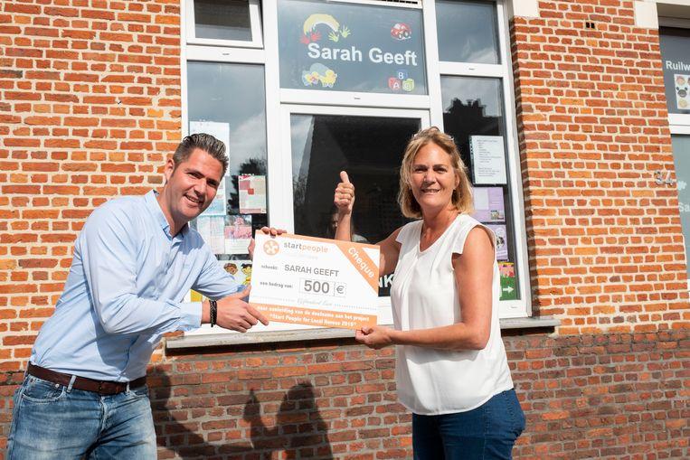 Bram Speltinckx overhandigt de cheque aan zijn zus Sarah die in september met Sarah Geeft startte.
