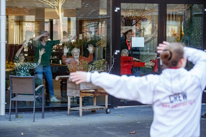 Zevenbergen - 25-3-2020- Foto: Pix4Profs/Marcel Otterspeer - De ouderen moeten door de coronacrisis binnen blijven. Trainers van Pals Fysio & Fitness trakteerden de bewoners van De Zeven Schakels op een bewegingsles, veilig aan de andere kant van de ramen.