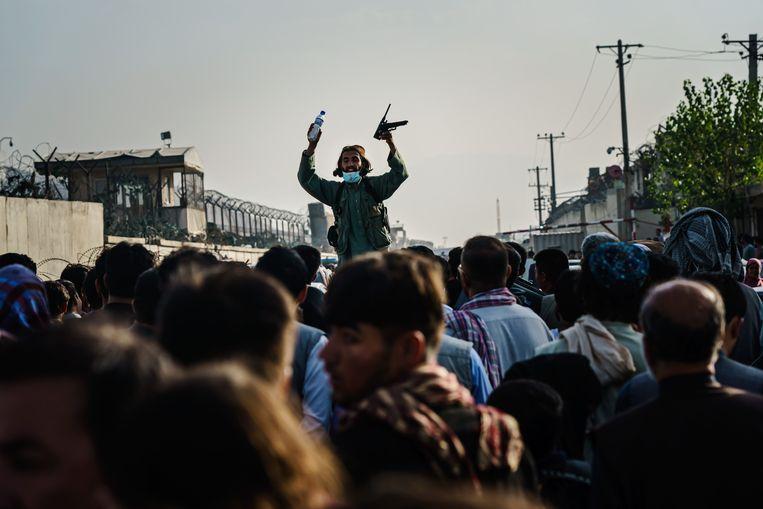 Een Talibanstrijder legt uit aan de menigte hoe de checkpointprocedure werkt voor de militaire weg naar de luchthaven van Kabul.  Beeld Los Angeles Times via Getty Imag