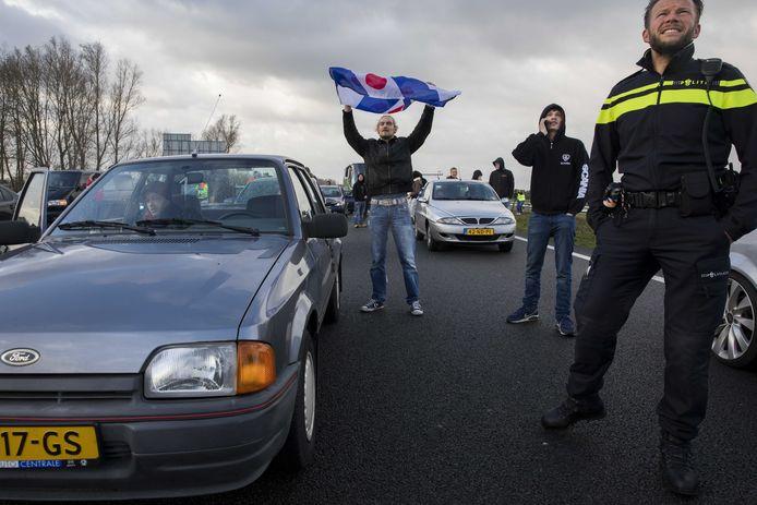 Een voorstander van Zwarte Piet zwaait met de Friese vlag . Hij blokkeert mee de snelweg. De politie grijpt niet in.