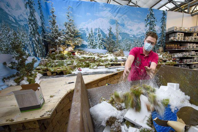 Een Intratuin-medewerker smijt de restanten van de besneeuwde kerstheuvels in de container. In de opbouw van de miniatuurdorpen ging weken zitten.