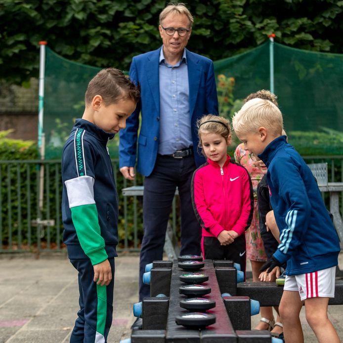 Kinderen doen e-game met lichtjes tijdens Sport en cultuurimpuls op basisschool St Marie, onder toeziend oog van wethouder Lars van der Beek