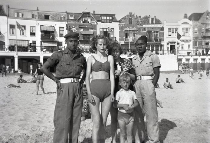 De ex-KNIL-soldaten Hiskia Kobrua (rechts) en A. Unawekla met een groep kinderen op het Badstrand van Vlissingen. Kobrua en Unawekla behoorden tot de eerste Molukkers die in Zeeland kwamen wonen, op 10 april 1951.