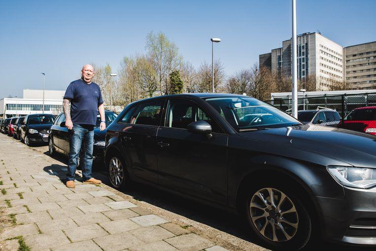Dirk Van Belle overdag in een Arduinstraat vol geparkeerde wagens.