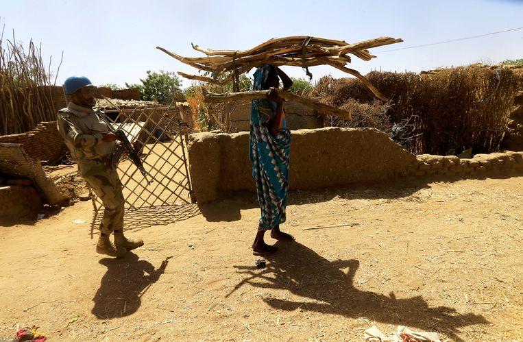 Een blauwhelm van van de VN-vredesmacht in Unamid in Soedan escorteert een ontheemde vrouw die hout heeft verzameld bij het kamp Kalma, dat is ingericht voor Soedanezen die het geweld in de regio Darfur ontvlucht zijn. Beeld REUTERS