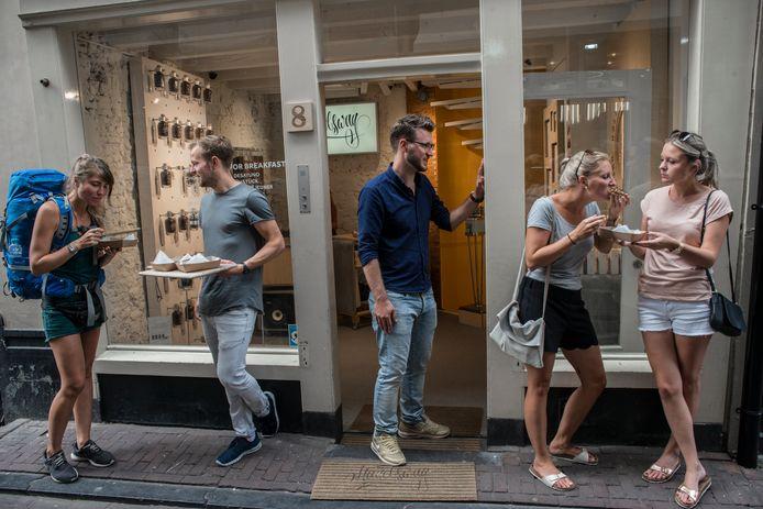 Lennart de Jong (grijs shirt) en Robbert Vos (met bril) delen boterhammen met hagelslag uit aan toeristen en voorbijgangers.