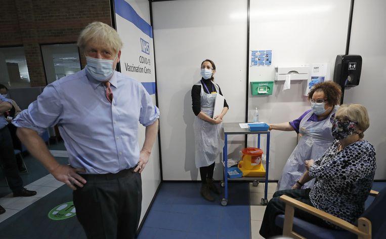 Boris Johnson praat met Lyn Wheeler (r), voordat ze als eerste het Pfizer-vaccin krijgt toegediend in het Guy's Hospital in Londen. Beeld Photo News