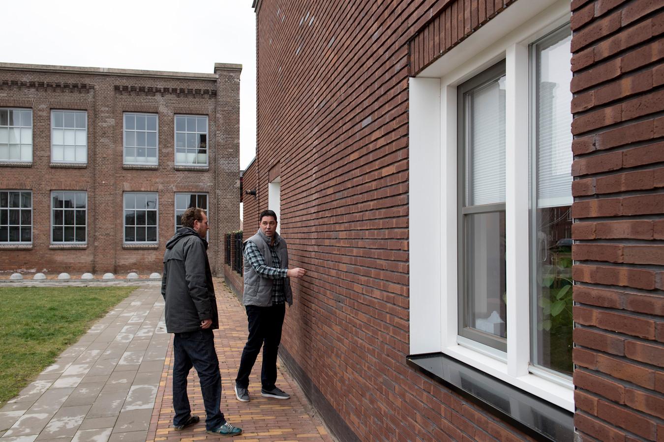 Bewoner Jan Willem van der Veen en bouwdeskundige Danny Veerman op het Enka-terrein in Ede. De woningen voldoen niet aan de bouwvergunning, constateerde de toezichthouder.