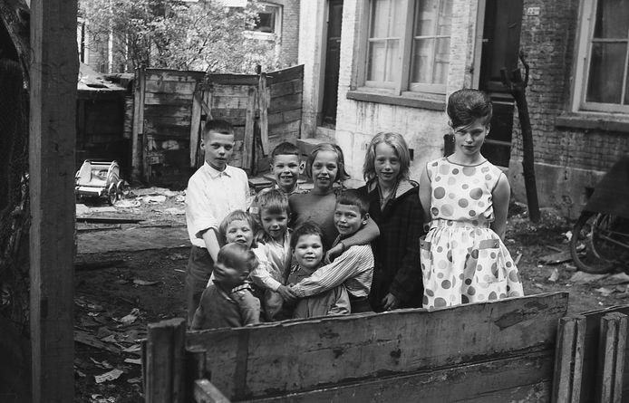 Omgeving Oranjeboomstraat, 1962. Een zeer gemêleerd gezelschap poseert voor Tjemmes.