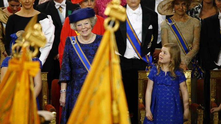 Prinses Alexia naast haar grootmoeder Beatrix tijdens de inhuldiging van Willem-Alexander als koning. Beeld anp
