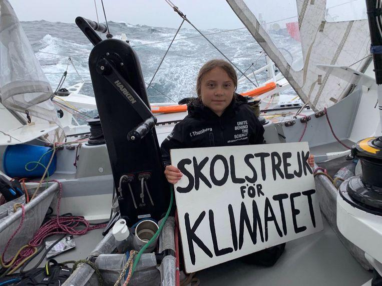 Zweedse klimaatactiviste Greta Thunberg eerder deze week met haar bordje waarop 'Skolstrejk för klimatet' gekalkt staat, tijdens haar zeiltocht over de Atlantische Oceaan naar de klimaattop in New York. Beeld EPA