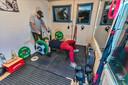 Marc van Tilburg uit Breda (staand) heeft een fitnessruimte ingericht in een schuurtje in zijn achtertuin. Hier is hij er aan het trainen met Cees Wisse.