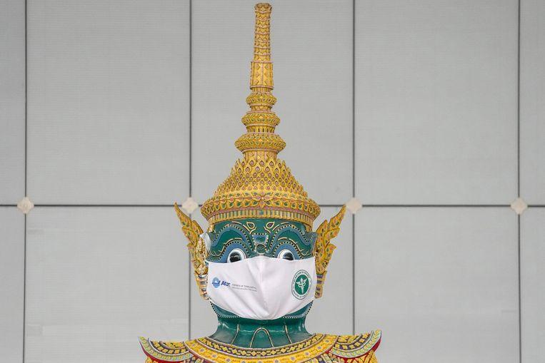 Ook een groot hindoeïstisch Ramayana-standbeeld op het vliegveld van Bangkok draagt een mondkapje. Beeld AP