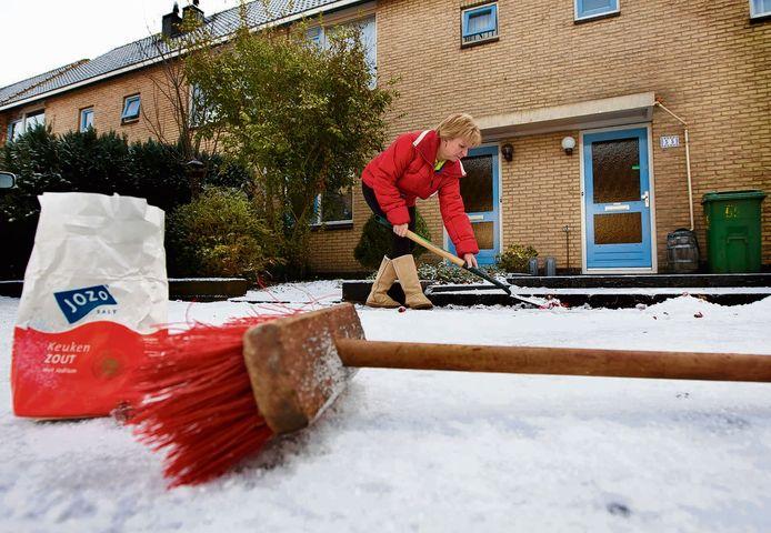 Een vrouw veegt haar stoep en maakt de ingang sneeuw en ijsvrij.