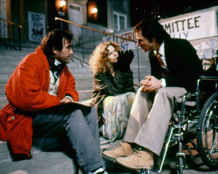 Oliver Stone (links) met Kyra Sedgwick en Tom Cruise op de set van Born on the Fourth of July (1989). Beeld Getty