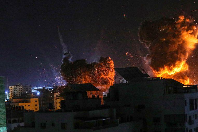 Vuur en rook stijgt op boven gebouwen in Gaza.  Beeld Getty Images
