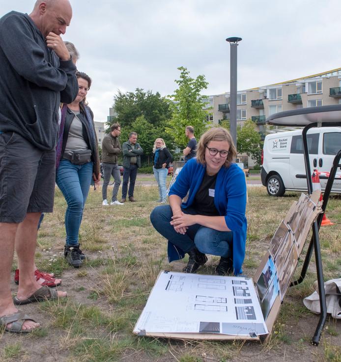 Demi Martens toont de ontwerpen van haar tiny house aan belangstellenden uit Drielanden, op de plek waar ze haar huis gaat bouwen in 2020. Het huis van Demi wordt verwarmd met een rocket stove, die op de achtergrond staat te branden.