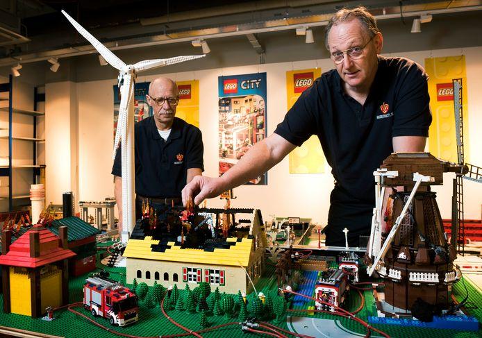 Brandweermannen Evert de Graaf (rechts) en André Overeem bij hun IncidentenCity van Lego, met de boerderij in Leerdam die onlangs afbrandde.