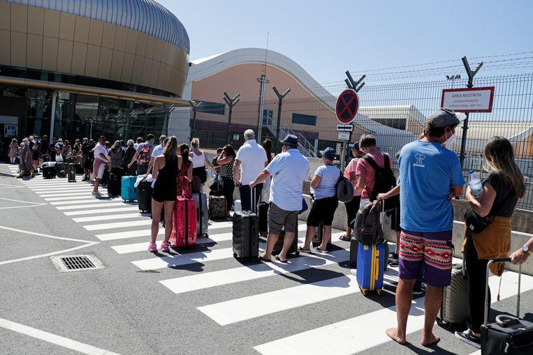 Britse toeristen en vakantiehuisbezitters staan massaal in de wachtrij op het vliegveld van Faro, nadat het reisadvies voor de Algarve flink was aangescherpt. Beeld EPA