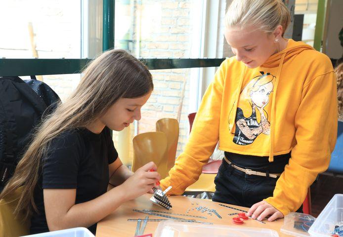 Charissa en Iris (beide 11) uit groep 8 leren een molen te malen van metalen onderdelen tijdens het Talent Atelier techniek en wetenschap.