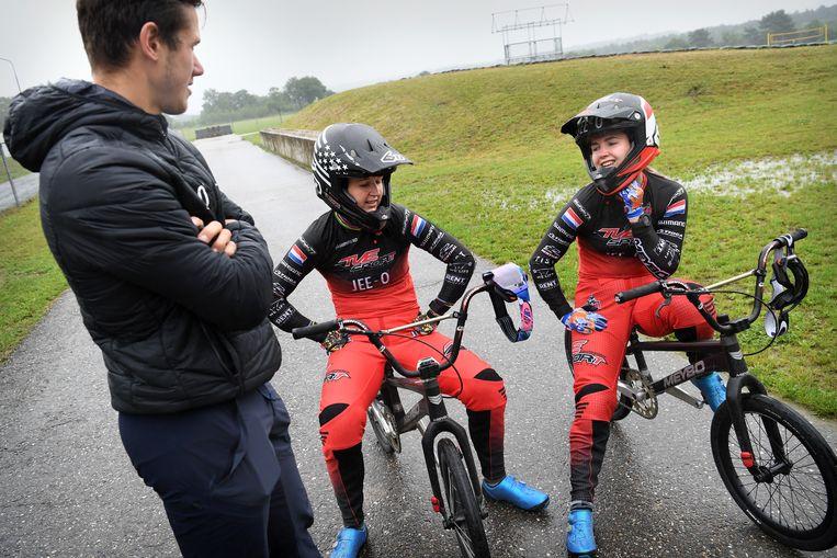 Laura en Merel Smulders praten tijdens de training met hun coach Klavs Lisovskis. Beeld Marcel van den Bergh