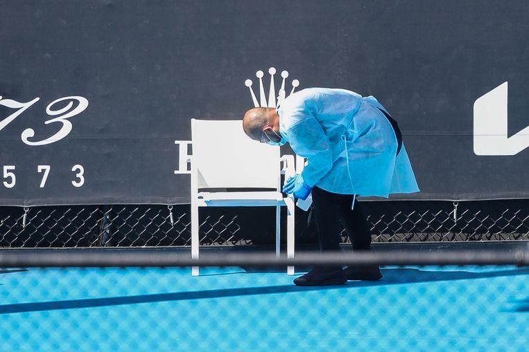 Een medewerker maakt op een van de banen van Melbourne Park, waar  tennissers kunnen trainen, een stoel schoon.  Beeld Getty Images
