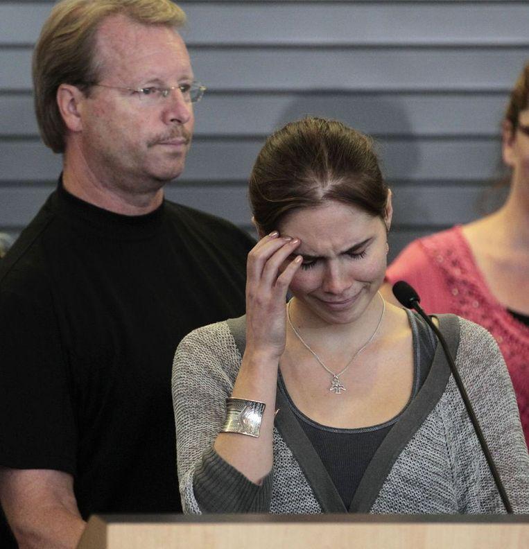 Een emotionele Amanda Knox bij een persconferentie als ze terugkomt in Seattle. Achter haar vader Curt Knox. Beeld ap