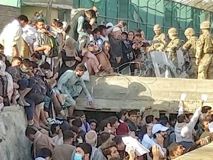 Wanhopige Afghanen proberen toegang tot de luchthaven van Kaboel te krijgen.