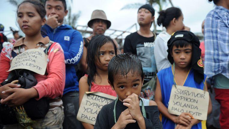 Overlevenden wachten op het vliegveld van Tacloban op een militair vliegtuig dat ze naar veiliger gebied zal brengen. Beeld afp