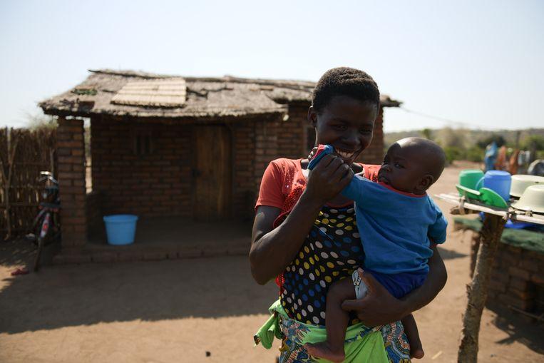 Violet Wilson (26) en haar zoontje (5 maanden) bij hun nieuwe stenen huis, dat beter beschermt tegen de muggen die malaria overbrengen. Beeld Thoko Chikondi