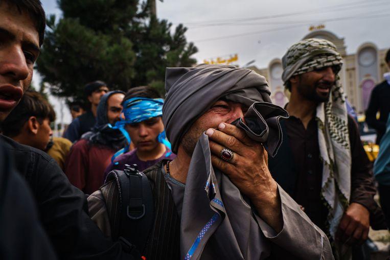 Een Afghaanse man kijkt vol afschuw naar talibanstrijders die met vuurwapens, zwepen en stokken de menigte te lijf gaan in de buurt van de internationale luchthaven in Kaboel.  Beeld Photo News