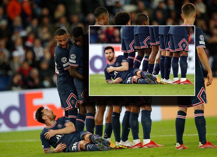 Lionel Messi ligt achter het PSG-muurtje. Neymar lijkt een lach niet te kunnen onderdrukken.