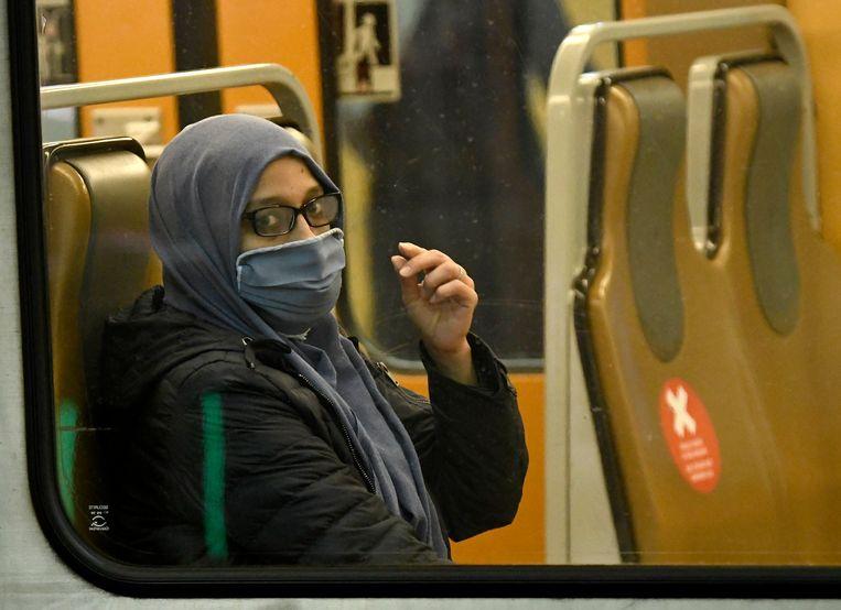 De mond wordt bedekt op de metro in Brussel. Beeld Photo News