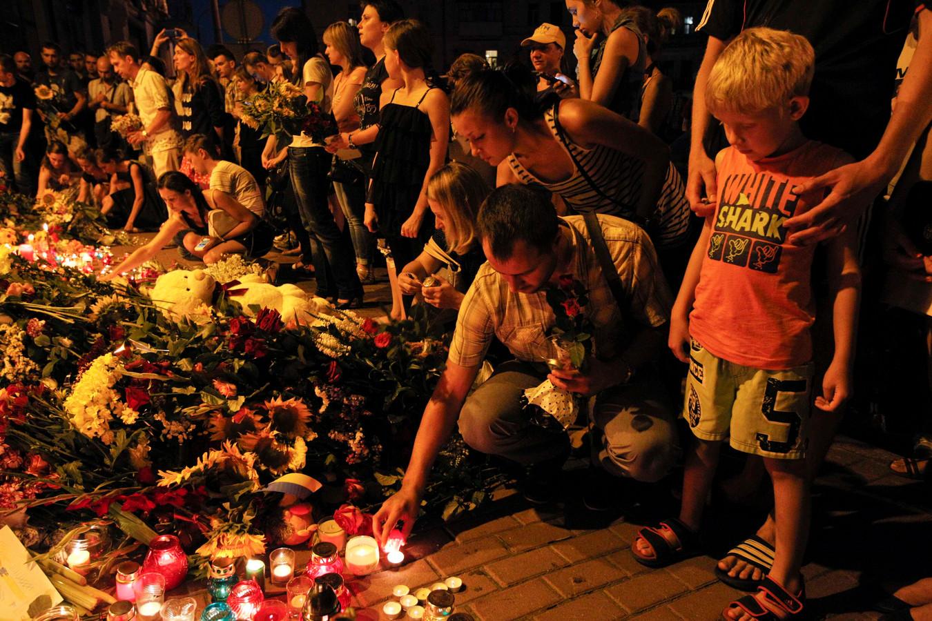 Mensen legden gisteren bloemen en staken kaarsjes aan bij de Nederlandse ambassade in Kiev.