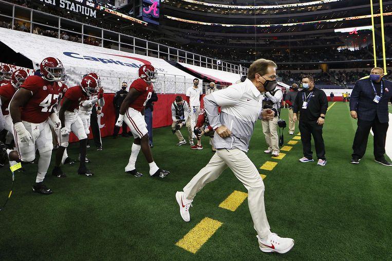 Coach en spelers van de Alabama Crison Tide komen het veld op voor de halve finale van de playsoffs van de competitie voor universiteitsteams. Beeld AFP