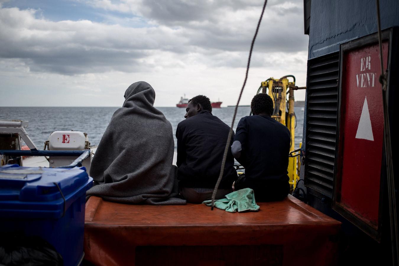 Drie van de migranten kijken uit over het water.