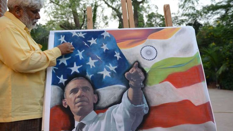 Een Indiase kunstenaar legt de laatste hand aan een schilderij met daarop president Obama, vorige week in Ahmedabad Beeld AFP