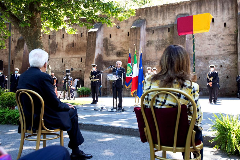 De ceremonie aan de oevers van de Tiber, met het gewraakt naambord dat bedekt werd gelaten. De verkeerd gespelde naam was door de aanwezigen te ontwaren door het vlaggedoek heen. Beeld AFP