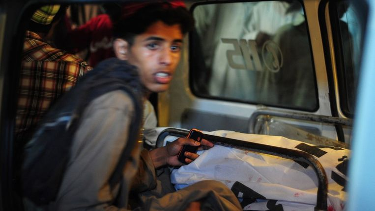 Een jongen naast een slachtoffer van de bomaanslag in Karachi. Beeld afp