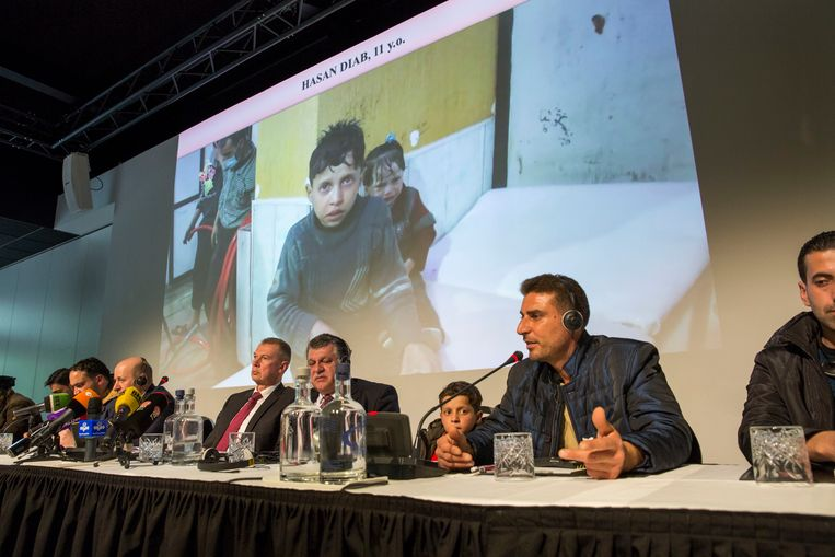 De kleine Hassan (11) luistert naar zijn vader op de persconferentie over de aanval op Douma. Beeld Arie Kievit
