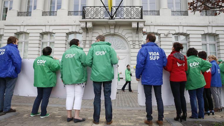 De vakbonden trokken deze ochtend naar het Martelaarsplein om er minister van Onderwijs Hilde Crevits en minister-president Geert Bourgeois twee banners te overhandigen. Beeld BELGA