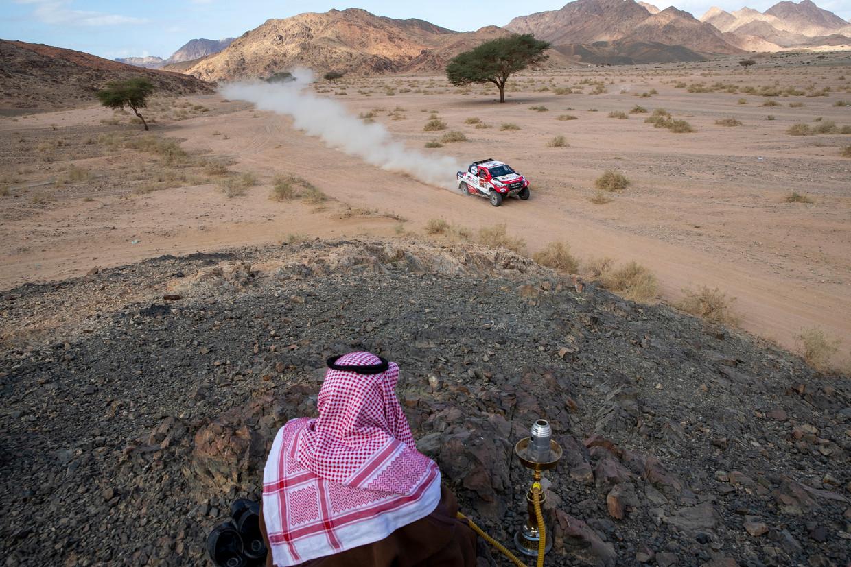 Een man ziet hoe topcoureur Fernando Alonso voorbijraast in zijn Toyota tijdens de Dakar 2020. Die rally vindt dit jaar plaats in Saudi-Arabië.