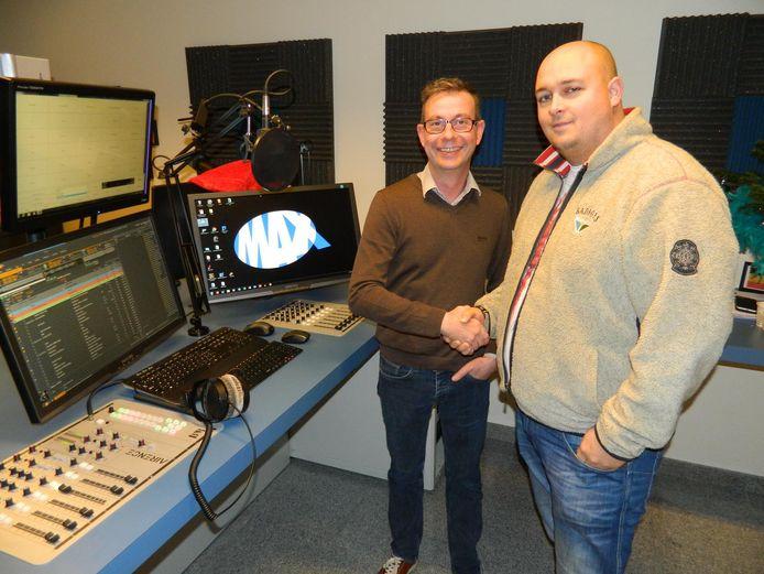Stationmanager Wim Van Geert (links) schudt de hand van Filip Van de Genachte van Meetjesland FM.