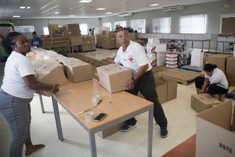 Vrijwilligers van het Rode Kruis op Curaçao vullen voedsel- en andere hulppakketten, bedoeld voor mensen die hun baan zijn kwijtgeraakt door de coronacrisis. Beeld ANP