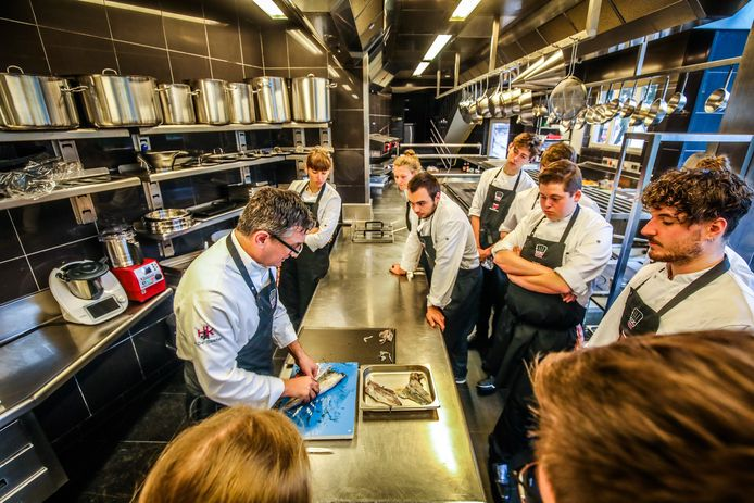 De studenten aan de opleiding Culinary Arts kijken geboeid toe hoe docent Peter De Coster een vis fileert.