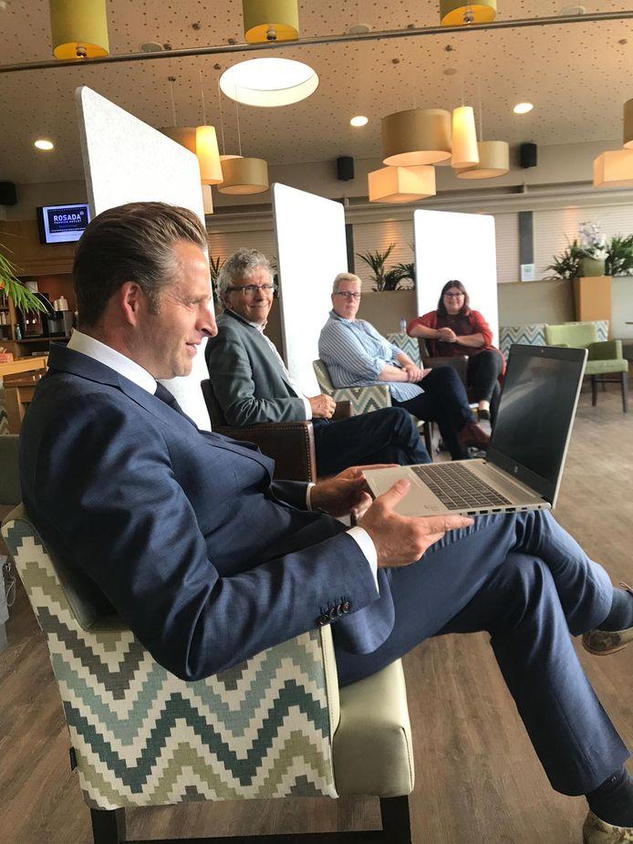 Minister Hugo de Jonge spreekt via de laptop bij het Parkhuis in Dordrecht met een bewoner en een familielid.